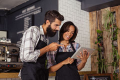 Smiling waiter and waitress interacting while using digital tablet Royalty Free Stock Images