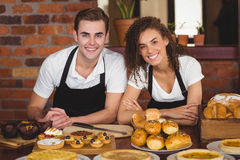 Smiling waiter and waitress leaning on counter royalty free stock photo