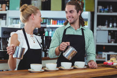 Smiling waiter and waitress making cup of coffee at counter Stock Images