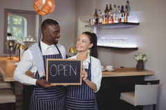 Smiling waiter and waitress showing chalkboard with open sign at counter Stock Photo
