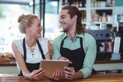 Smiling waiter and waitress standing at counter using digital Royalty Free Stock Photos