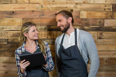 Smiling waiter and waitress using digital tablet against wooden wall Stock Photo