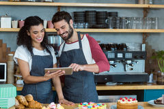 Smiling waiter and waitress using digital tablet at counter Royalty Free Stock Images