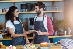 Smiling waiter and waitress using digital tablet at counter Stock Photo