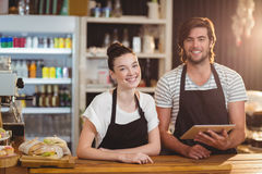 Smiling waiter and waitress using digital tablet at counter Stock Photos