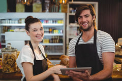 Smiling waiter and waitress using digital tablet at counter. In cafe Royalty Free Stock Photos