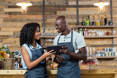 Smiling waiter and waitress using digital tablet at counter Stock Photography