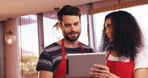 Smiling waiter and waitress using digital tablet stock video