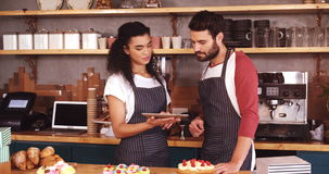 Smiling waiter and waitress using digital tablet at counter. In cafe 4k stock video