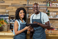 Smiling waiter and waitress using digital tablet at counter in cafe Stock Image