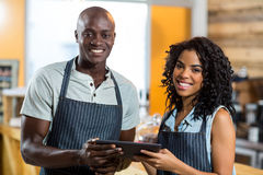 Smiling waiter and waitress using digital tablet at counter in cafe Stock Images