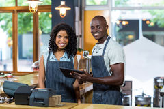 Smiling waiter and waitress using digital tablet at counter in cafe Royalty Free Stock Image
