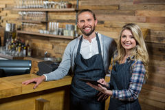Smiling waiter and waitress using digital tablet at counter in cafe Royalty Free Stock Photos
