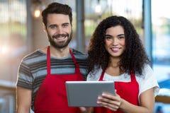 Smiling waiter and waitress using digital tablet at counter. Portrait of smiling waiter and waitress using digital tablet at counter in cafe Stock Photo