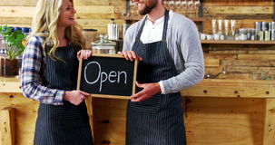 Smiling waiter and waitresses holding open sign board. In caf stock video footage