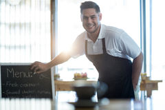 Smiling waiter writing on menu board in cafe Stock Photography