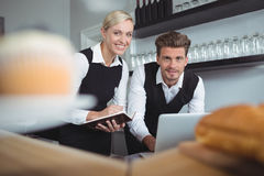 Smiling waiters using laptop at counter in restaurant Stock Photography
