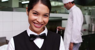 Smiling waitress being handed a dish by chef stock video