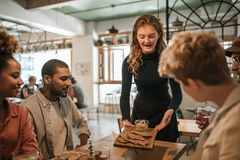 Smiling waitress bringing food to a table of customers stock photo