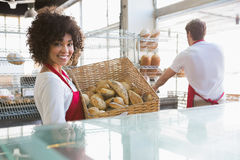 Smiling waitress carrying basket of bread Royalty Free Stock Photo