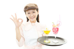 Smiling waitress carrying a cocktail Stock Photography