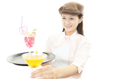 Smiling waitress carrying a cocktail Royalty Free Stock Images