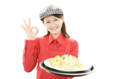 Smiling waitress carrying a meal Stock Images