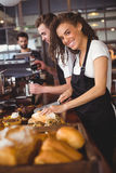 Smiling waitress cutting bread in front of colleague Stock Image
