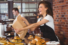 Smiling waitress giving paper bag to customer. At coffee shop Royalty Free Stock Image