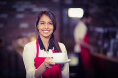 Smiling waitress handing a cup of coffee Stock Image