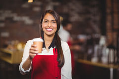 Smiling waitress handing a take-away mug. Portrait of a waitress handing a take-away mug at the coffee shop Royalty Free Stock Images