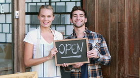 Smiling waitress and hipster man holding open signboard