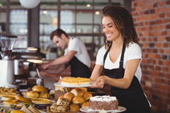 Smiling waitress holding cake in front of colleague. At coffee shop Royalty Free Stock Photography