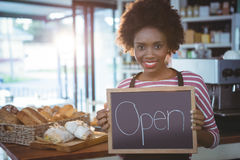 Smiling waitress holding chalkboard with open sign Stock Photos