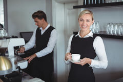 Smiling waitress holding cup of coffee at counter Stock Images