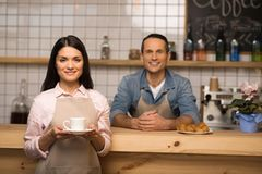 Waitress holding cup of coffee. Smiling waitress holding cup of coffee and looking at the camera with barista on the background Stock Photography