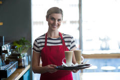 Smiling waitress holding cup of cold coffee at counter in cafe Royalty Free Stock Photos