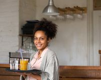 Smiling waitress holding tray of drinks in restaurant. Portrait of a smiling waitress holding tray of drinks in restaurant Royalty Free Stock Image