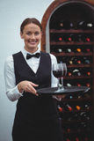 Smiling waitress holding a tray with glasses of red wine Royalty Free Stock Images