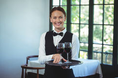 Smiling waitress holding a tray with glasses of red wine Royalty Free Stock Image