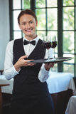 Smiling waitress holding a tray with glasses of red wine Stock Photography
