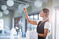 Smiling waitress holding up a empty wine glass. In restaurant royalty free stock photo
