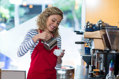 Smiling waitress making cup of coffee at counter Stock Image