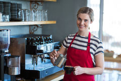 Smiling waitress making cup of coffee at counter in cafe Stock Photos