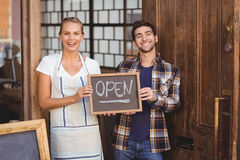 Smiling waitress and man holding chalkboard with open sign Stock Photo