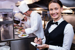 Smiling waitress with note pad in commercial kitchen Royalty Free Stock Photos