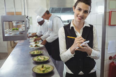 Smiling waitress with note pad in commercial kitchen. Portrait of smiling waitress with notepad in commercial kitchen and chefs preparing food in background stock photography