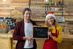 Smiling waitress and owner standing with merry x mas sign board in cafe Royalty Free Stock Images