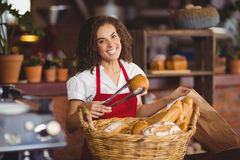 Smiling waitress picking up bread from a basket Royalty Free Stock Photos