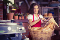 Smiling waitress putting bread in a paper bag Stock Photo